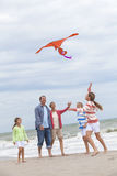 Family Parents Girl Children Flying Kite on Beach. Happy family mother, father, daughter, parents and female girl children flying a red kite, playing & laughing Royalty Free Stock Photography