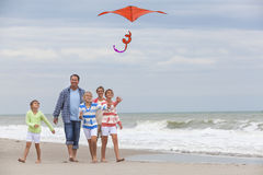 Family Parents Girl Children Flying Kite on Beach. Happy family mother, father, daughter, parents and female girl children flying a red kite, playing & laughing Royalty Free Stock Photo