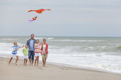 Family Parents Girl Children Flying Kite on Beach. Happy family mother, father, daughter, parents and female girl children flying a red kite, playing & laughing Stock Photos