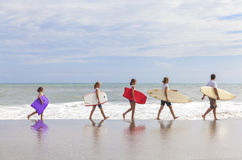 Family Parents Girl Children Surfboards on Beach. Rear view of family mother, father, daughter, parents and female girl children going surfing with surfborards Royalty Free Stock Image