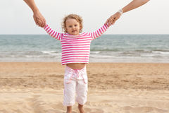 Family parents are holding baby's hands on beach Royalty Free Stock Photos