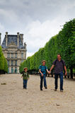 Family in Paris. Tourists, a father and his two kids walking in a lane in the Tuilleries Gardens in Paris with the Louvre museum in the background Royalty Free Stock Photography