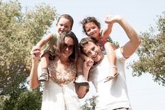 Family in the park. Parents with children sitting on the shoulders royalty free stock photo