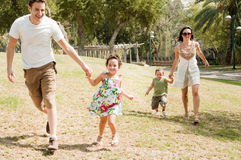 Family in the park. Family running with two young children at the park stock photo