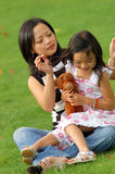Family in the park. Caring Mother sorting out daughter's hair Royalty Free Stock Photography