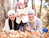 Family in the park. Happy young family with their daughter spending time outdoor in the autumn park (focus on the women stock image