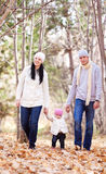 Family in the park. Happy young family with their daughter spending time outdoor in the autumn park (focus on the men and women royalty free stock photography