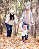 Family in the park. Happy young family with their daughter spending time outdoor in the autumn park (focus on the men and child royalty free stock photos