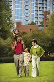 Family in park. Family of four people walking in park smiling royalty free stock image