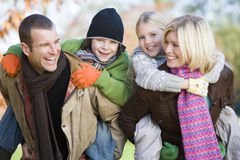 Family At The Park. Parents outdoors piggybacking two young children and smiling Stock Photography