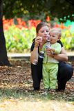Family in park blows bubbles. Young woman with her son blows bubbles in a city park Royalty Free Stock Photos