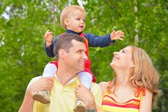 Family in park with child on shoulders royalty free stock images