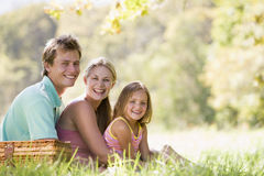Family at park having a picnic and smiling. At camera Stock Images
