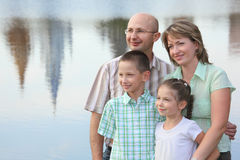Family in park on pond background. Family in park. father, mother, little girl and little boy on pond background. man is embracing his wife Royalty Free Stock Images