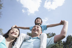 Family in park with son on father's shoulders. Stock Photography