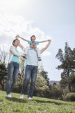 Family in park with son on father's shoulders. stock photos