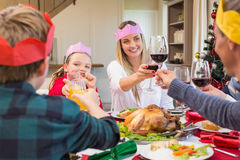 Family in party hat toasting at christmas dinner Stock Photos