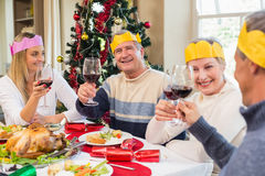 Family in party hat toasting at christmas dinner Royalty Free Stock Photography