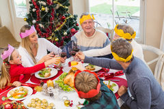 Family in party hat toasting at christmas dinner Royalty Free Stock Images
