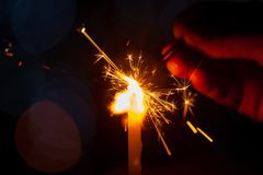 Family party woman holding and playing with fire sparklers royalty free stock images
