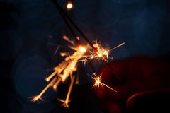 Family party woman holding and playing with fire sparklers royalty free stock photography