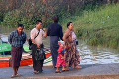 Family passenger walk together from Myanmar traditional ferry across Yangon river on the morning stock images