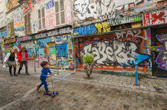 Family passes by dazzling street art on Rue Denoyez in Paris Royalty Free Stock Photo