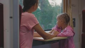 Family passing the time on train journey in Asia, looking to window and talking. Happy family passing the time on train journey in Asia. Young mother with little stock video