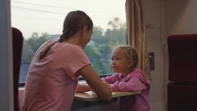 Family passing the time on train journey in Asia, looking to window and talking. Happy family passing the time on train journey in Asia. Young mother with little stock video footage