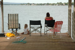 Family Past Time. A family sits on the dock together fishing and hanging out at the lake for the weekend. A weekend family get away Stock Photo