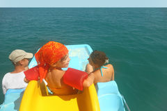 Family on pedal boat with slide in sea Royalty Free Stock Photo