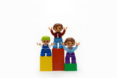 Family on the pedestal. Family of plastic dolls stands on the pedestal Royalty Free Stock Image