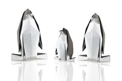 Family of penguins. Family of origami penguins on the white reflection background Stock Images