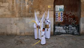 A family of penitents preparing before the start of an easter holy week procession in mallorca detail on hoods detail. Penitents of the same family prepare stock images