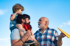 Family people. Airplane ready to fly. Male multi generation family. Kid pilot with toy jetpack against sky background royalty free stock images