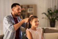 Father braiding daughter hair at home. Family and people concept - happy father braiding daughter hair at home royalty free stock photos