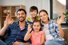 Portrait of happy family waving hands at home. Family and people concept - portrait of happy father, mother, little son and daughter waving hands at home royalty free stock images