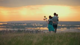 Family of 3 people resting in nature, mom dad and son go and cuddle, orange sunset. Telephoto shot stock video