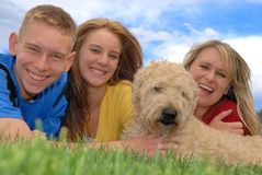 Family With Pet. Family laying on grass area with their wheaten terrier dog Royalty Free Stock Photography