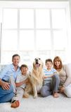 Family with pet. Cheerful family with their pet sitting on the floor at home Royalty Free Stock Photos