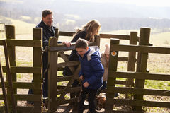 Family and pet dog passing through a gate in the countryside Royalty Free Stock Photography