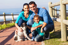 Family pet dog. Portrait of lovely family and pet dog outdoors at beach Stock Images