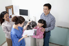 Family with pet dog in veterinarian's office Stock Photo