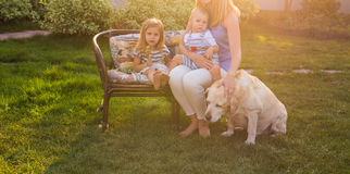 Family, pet, domestic animal and people concept - happy family with labrador retriever dog summer garden royalty free stock photo