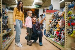 Family in pet shop, happy customers. Father, mother and little daughter chooses domestic animal in petshop Stock Photography