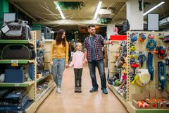 Family in pet shop, happy customers. Father, mother and little daughter chooses domestic animal in petshop Stock Image