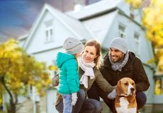 Happy family with dog over house in autumn. Family, pets and people concept - happy mother, father and little daughter with beagle dog outdoors over house in stock image