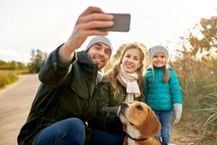 Happy family with dog taking selfie in autumn. Family, pets and people concept - happy mother, father and little daughter with beagle dog taking selfie by stock photo