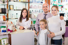 Family in the pharmacy. Cheerful smiling family of three happy persons getting help of a pharmacist in the pharmacy Royalty Free Stock Photos