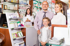 Family in the pharmacy. Cheerful smiling family of three persons getting help of pharmacist in a pharmacy Royalty Free Stock Photo